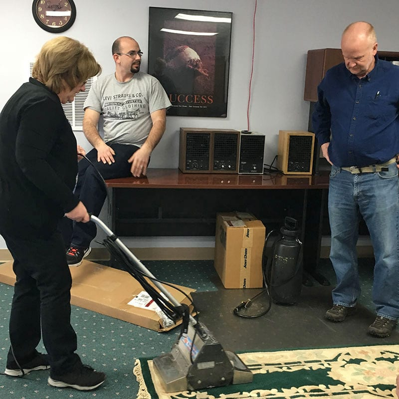 AmeriClean employees training with a rug cleaner