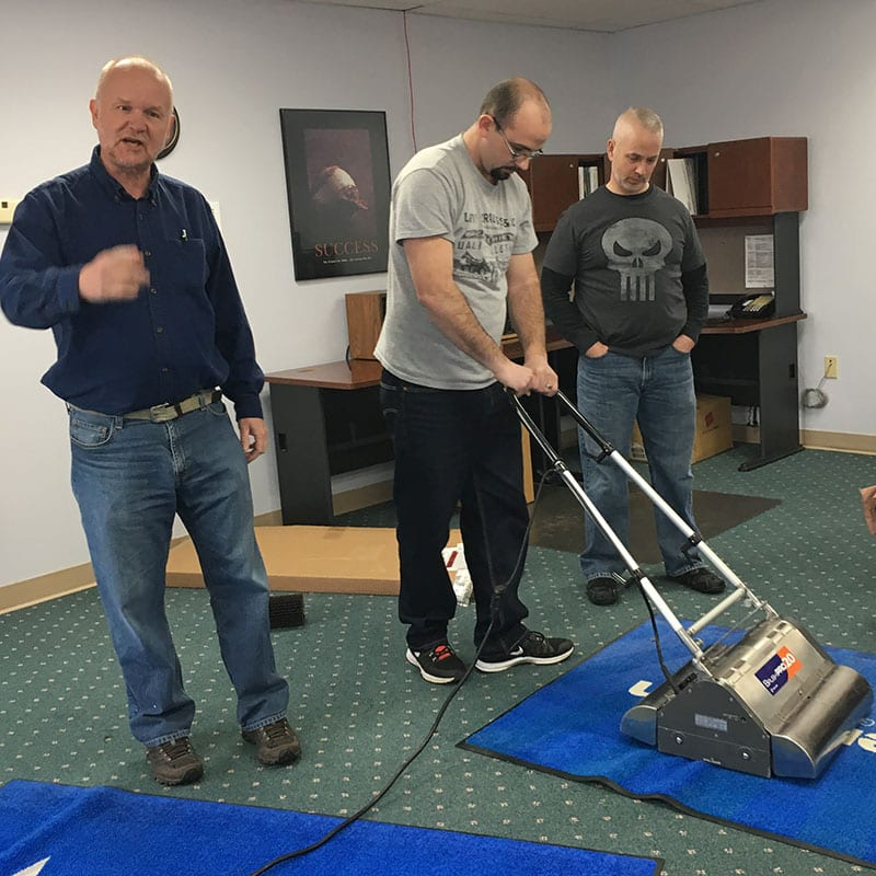 AmeriClean employees training with a carpet cleaner